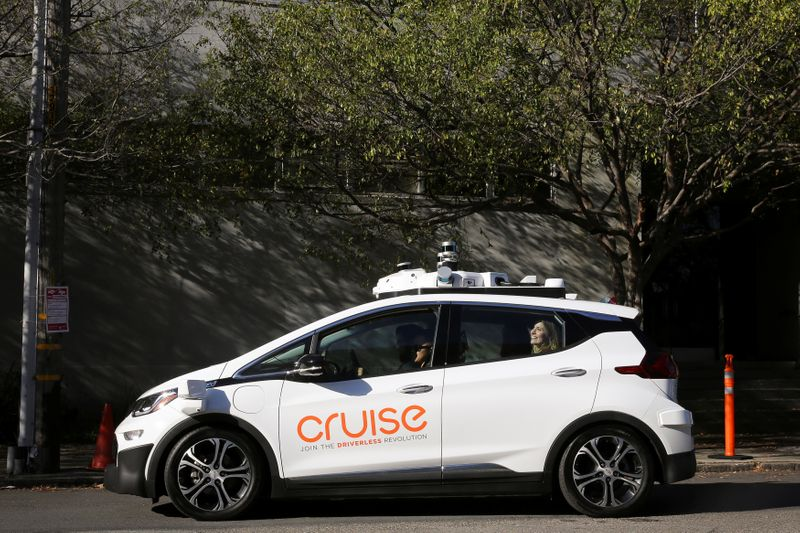 A woman smiles in the back seat of a self-driving Chevy Bolt EV car during a media event by Cruise, GM's autonomous car unit,  in San Francisco