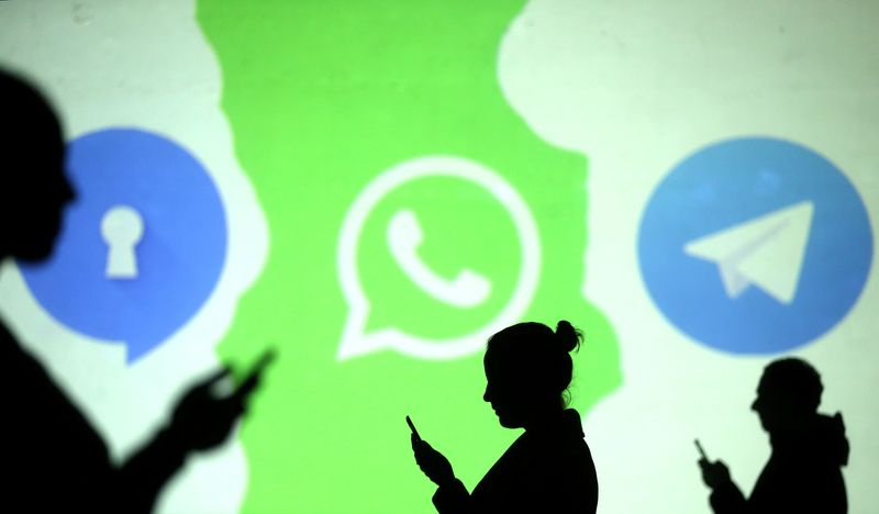 Silhouettes of mobile users are seen next to logos of social media apps Signal, Whatsapp and Telegram projected on a screen in this picture illustration