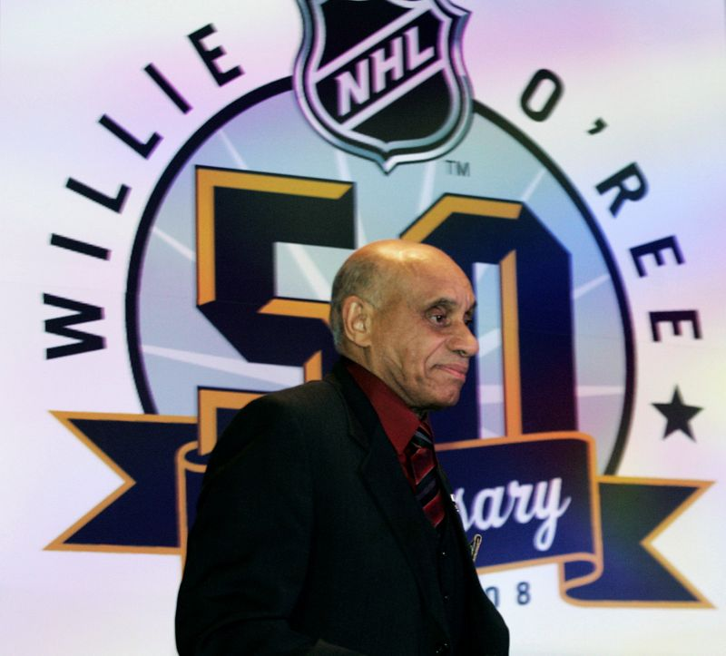 FILE PHOTO: First black hockey player Willie O'Ree stands on stage in front of a banner after a luncheon honoring O'Ree's 50th anniversary debut in the NHL in Atlanta.