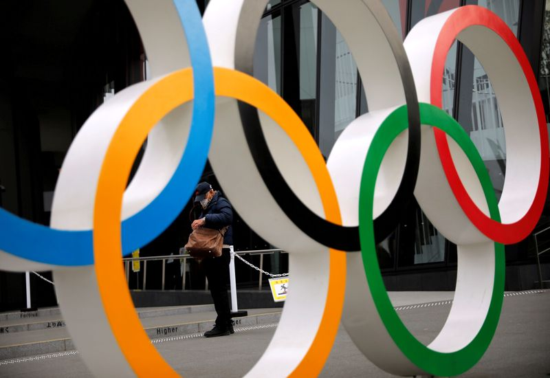 FILE PHOTO: Man is seen through the Olympic rings in Tokyo