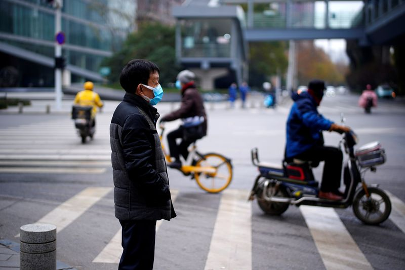 FILE PHOTO: Man wearing a mask stands near a street, almost a year after the start of the coronavirus disease (COVID-19) outbreak, in Wuhan, Hubei