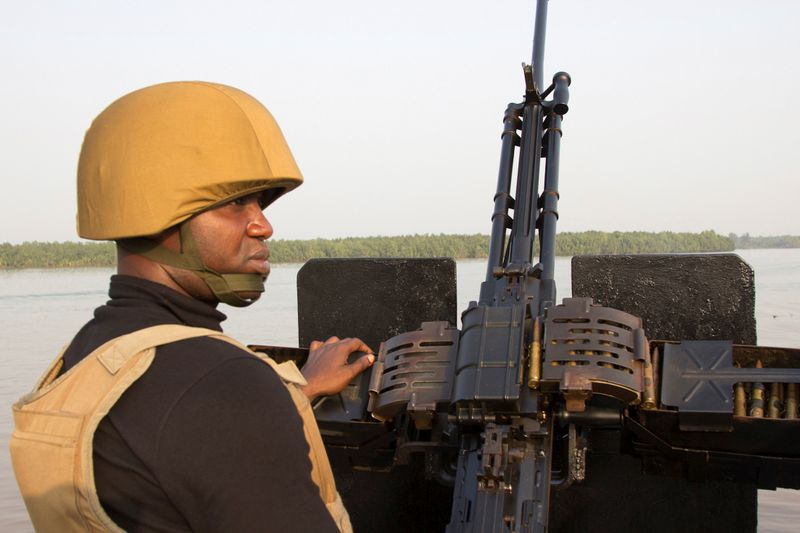 canFILE PHOTO: A naval officer mans a machine gun on a boat off the Atlantic coast in Nigeri's Bayelsa state
