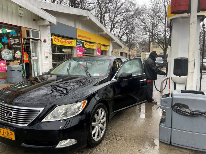 FILE PHOTO: Julio Barrios attends to a customer at a gas station in Scarsdale