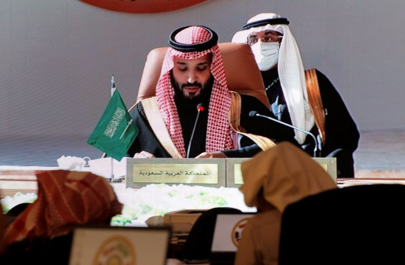 Saudi Arabia's Crown Prince Mohammed bin Salman is pictured via screen as he talks during the Gulf Cooperation Council's (GCC) 41st Summit, at the media centre in Al-Ula