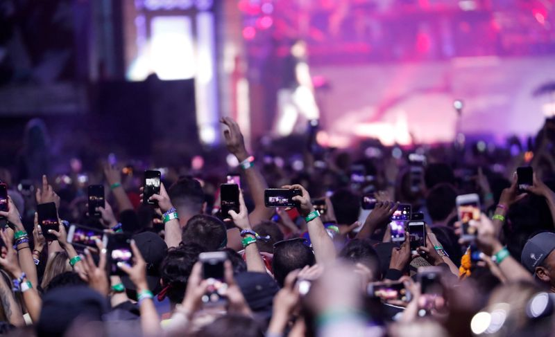 FILE PHOTO: Concertgoers use their mobile phones during Eminem's performance at the Coachella Valley Music and Arts Festival in Indio