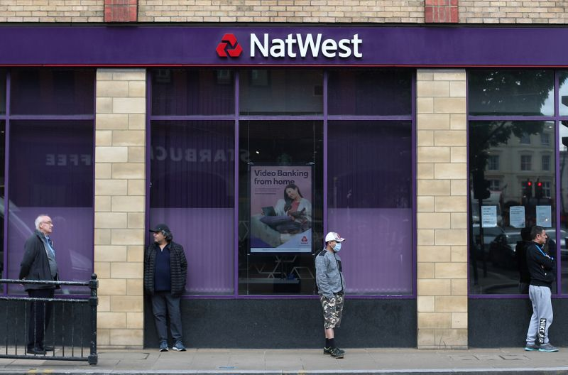 FILE PHOTO: People maintain social distance while they queue outside a Natwest bank in Wimbledon