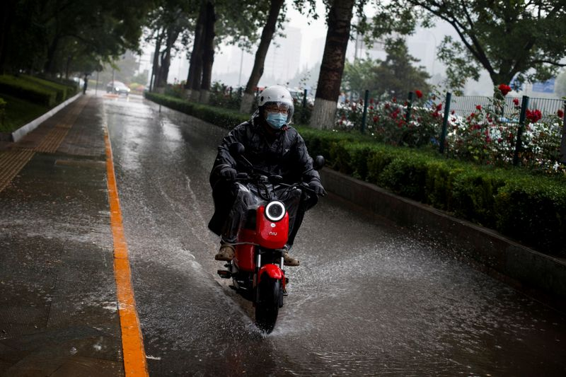 FILE PHOTO: A man rides a Niu electric scooter through a puddle as a sudden thunderstorm darkens the mid-afternoon sky in Beijing