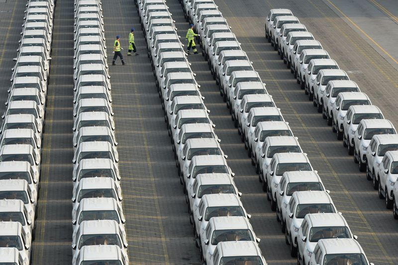 Workers walk among the newly arrived imported Toyota cars at the Shenzhen Dachan Bay Terminals in Guangdong