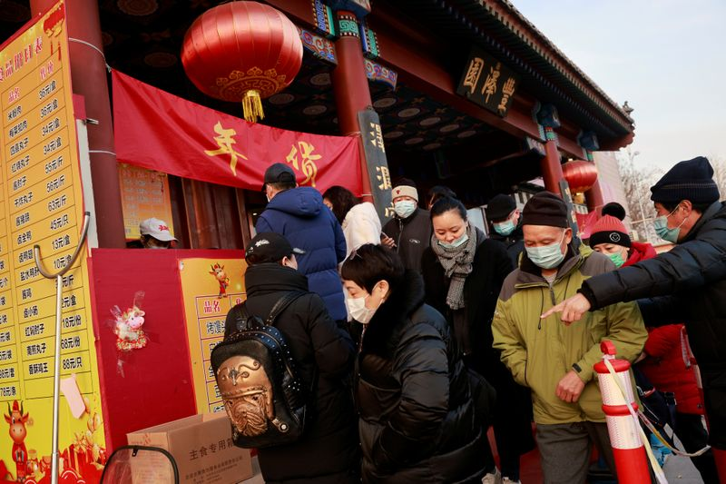 People line up at the street stall of Fengzeyuan restaurant to buy dishes typical for Lunar New Year celebrations following an outbreak of the coronavirus disease (COVID-19) in Beijing