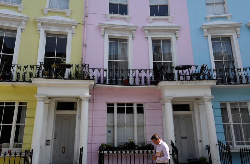 FILE PHOTO:  A man walks past houses painted in various colours in a residential street in London