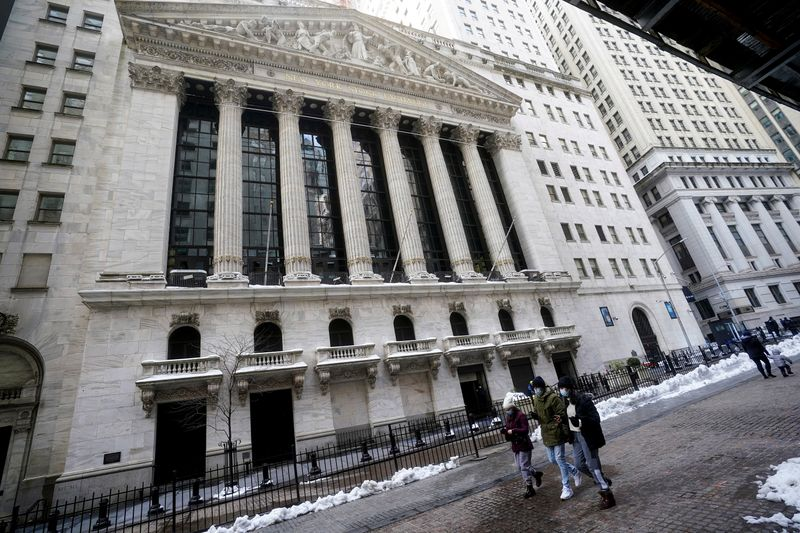 FILE PHOTO: People walk past the New York Stock Exchange in New York City