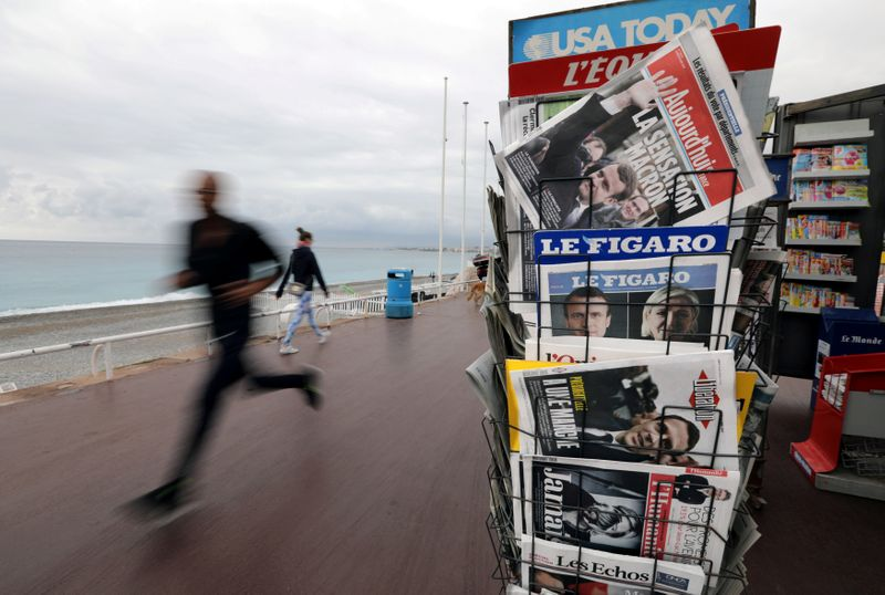 FILE PHOTO: A man jogs past a news rack which displayed copies of French newspapers with front pages about the results in France's Presidential election on the Promenade Des Anglais in Nice