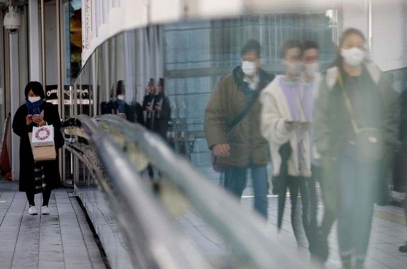 FILE PHOTO: Pedestrians walk on a street in Tokyo, Japan amid the COVID-19 outbreak