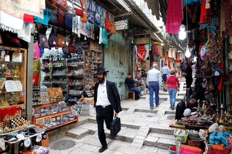 People walk around an alley in Jerusalem's Old City
