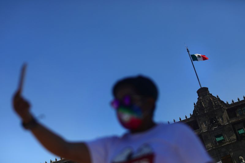 A man takes photos in front of National Palace in Mexico City
