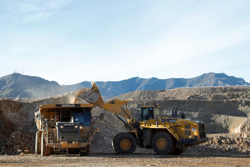A wheel loader operator fills a truck with ore at the MP Materials rare earth mine in Mountain Pass