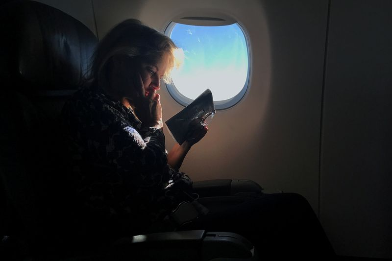FILE PHOTO: A woman reads while sitting in a business class seat on a flight from New York City to Washington D.C.