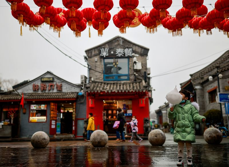 A girl eats cotton candy in a historic part of Beijing as China celebrates Lunar New Year of the Ox following an outbreak of the coronavirus disease (COVID-19)