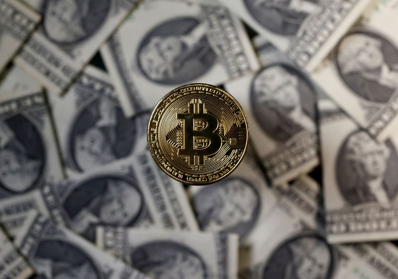 FILE PHOTO: A bitcoin (virtual currency) coin placed on Dollar banknotes is seen in this illustration picture