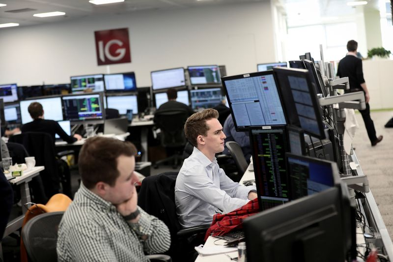 FILE PHOTO: Traders look at financial information on computer screens on the IG Index trading floor