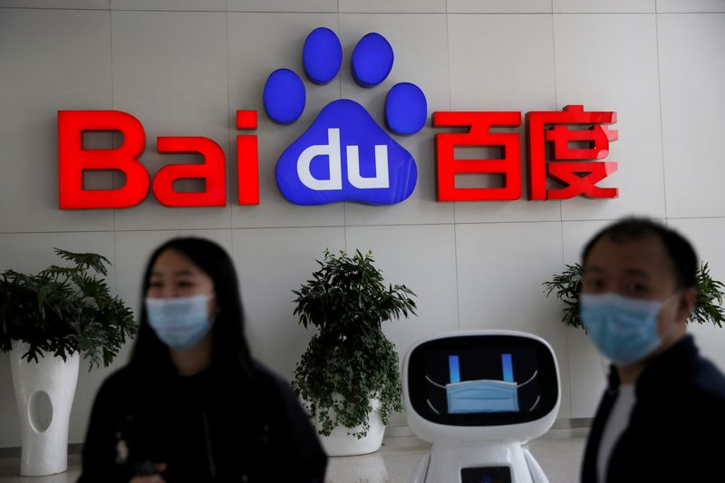 FILE PHOTO: Employees wearing face masks are seen next to a Baidu AI robot, in front of a sign of Baidu at the company's headquarters in Beijing