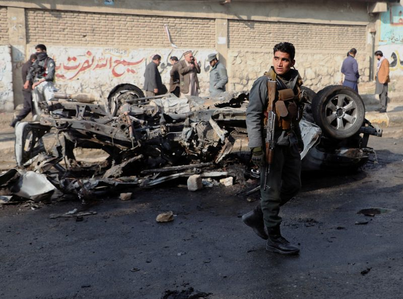 FILE PHOTO: An Afghan police officer keeps watch at the site of a bomb blast in Kabul