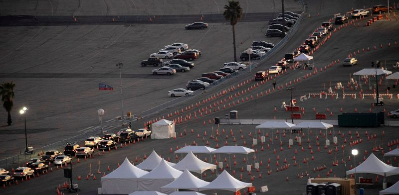 FILE PHOTO: Vehicles line up at Dodger Stadium COVID-19 vaccination site at sunset during the outbreak of the coronavirus disease (COVID-19), in Los Angeles