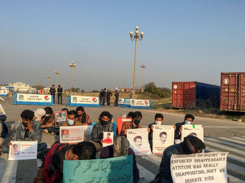 People hold signs and photos as they sit along a road demanding to know the details on the whereabouts of their missing family members, during a protest in Islamabad