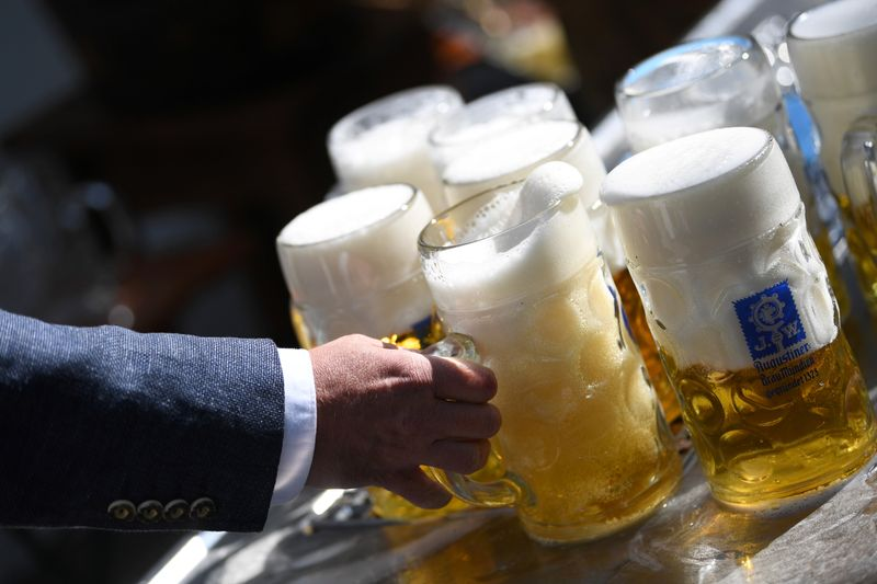 Beer garden manger attends to mugs during tapping of barrel near Theresienwiese, Munich