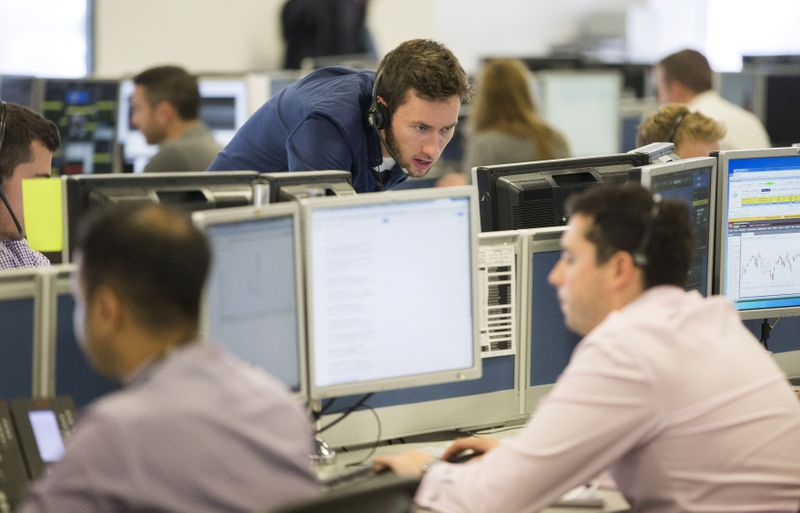 FILE PHOTO: Dealers work on the IG Group trading floor in London, Britain