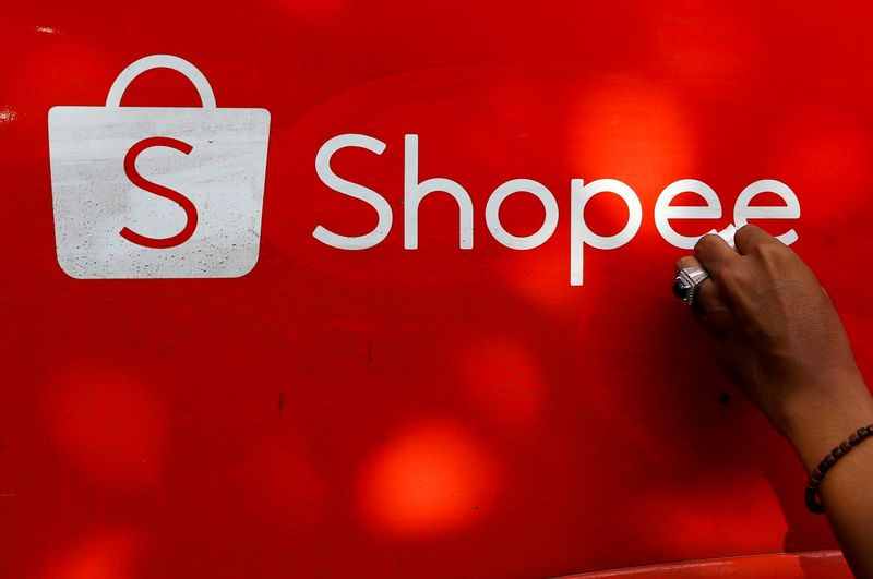 FILE PHOTO: A worker wipes the door of a car with the sign of Shopee, an Indonesian e-commerce platform, in Jakarta