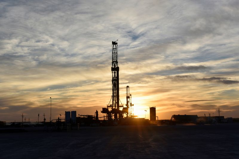 Drilling rigs operate at sunset in Midland