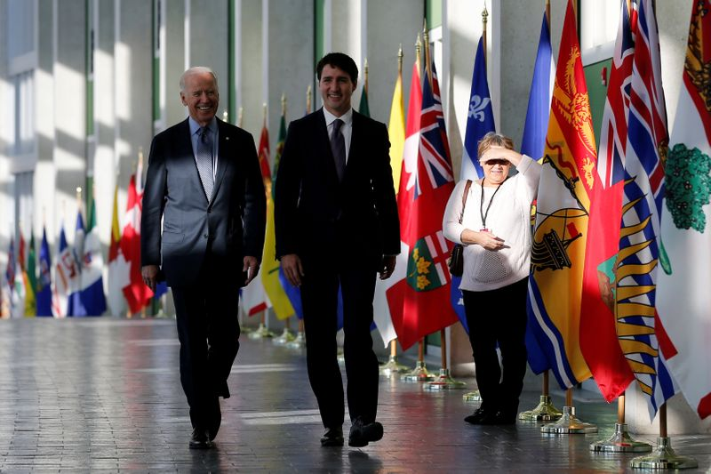 FILE PHOTO: A woman watches as U.S. Vice President Joe Biden and Canada's Prime Minister Justin Trudeau arrive at the First Ministers' meeting in Ottawa