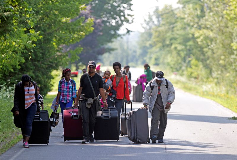 FILE PHOTO: Three families that claimed to be from Burundi walk down Roxham Road to cross into Quebec at the US-Canada border in Champlain, New York