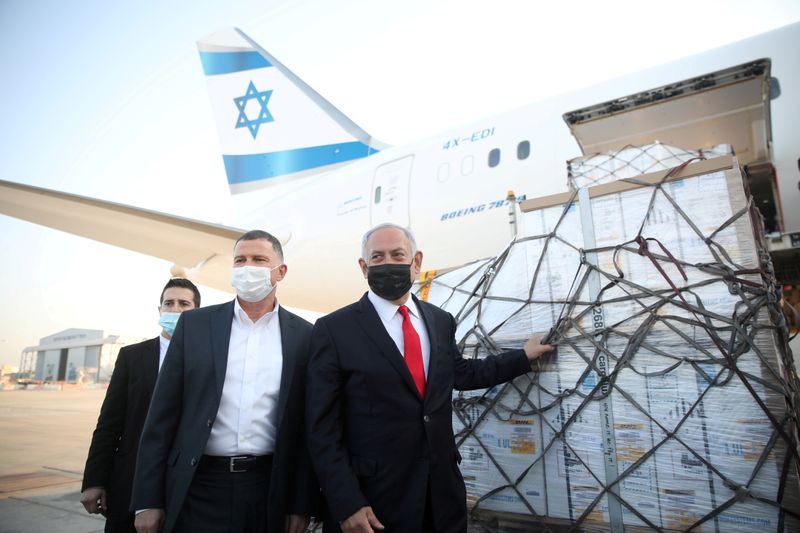 FILE PHOTO: Israel Prime Minister Benjamin Netanyahu and Health Minister Yuli Edelstein attend the arrival of a plane with a shipment of Pfizer-BioNTech COVID-19 vaccines, near the city of Lod