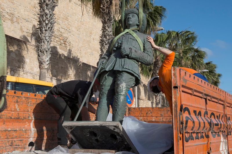 Local workers remove a statue of former Spanish dictator Francisco Franco in Spain