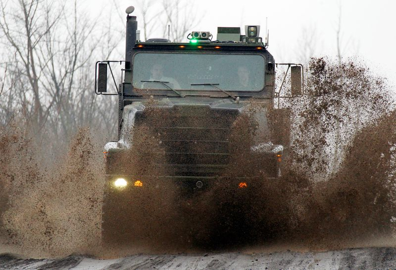 An Oshkosh truck using the TerraMax autonomous driving system drives along a mud-soaked test course outside of Pittsburgh