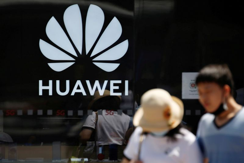 FILE PHOTO: People walk past a Huawei store at a shopping complex in Beijing