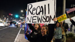 FILE — In this Nov. 21, 2020 file photo, demonstrators shout slogans while carrying a sign calling for the recall of Gov. Gavin Newsom during a protest against a stay-at-home order amid the COVID-19 pandemic in Huntington Beach, Calif. About a year after the state's first coronavirus case, Newsom has gone from a governor widely hailed for his swift response to a leader facing criticism from all angles. (AP Photo/Marcio Jose Sanchez, File)