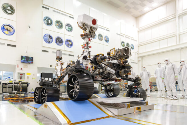 "FILE - In this Dec. 17, 2019 photo made available by NASA, engineers watch the first driving test for the Mars 2020 rover, later named ""Perseverance,"" in a clean room at the Jet Propulsion Laboratory in Pasadena, Calif. (J. Krohn/NASA via AP"