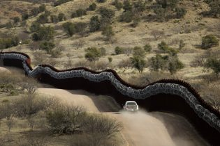 FILE - This March 2, 2019 photo shows a Customs and Border Control agent patrols on the US side of a razor-wire-covered border wall along the Mexico east of Nogales, Ariz. President Joe Biden rushed to send the most ambitious overhaul of the nation's immigration system in a generation to Congress and signed nine executive actions to wipe out some of his predecessor's toughest measures to fortify the U.S.-Mexico border. But a federal court in Texas suspended his 100-day moratorium on deportations. (AP Photo/Charlie Riedel,File)