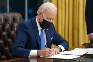 FILE - In this Feb. 2, 2021, file photo Joe Biden signs an executive order on immigration, in the Oval Office of the White House in Washington. Biden rushed to send the most ambitious overhaul of the nation's immigration system in a generation to Congress. And he signed nine executive actions to wipe out some of his predecessor's toughest measures to fortify the U.S.-Mexico border. (AP Photo/Evan Vucci, File)