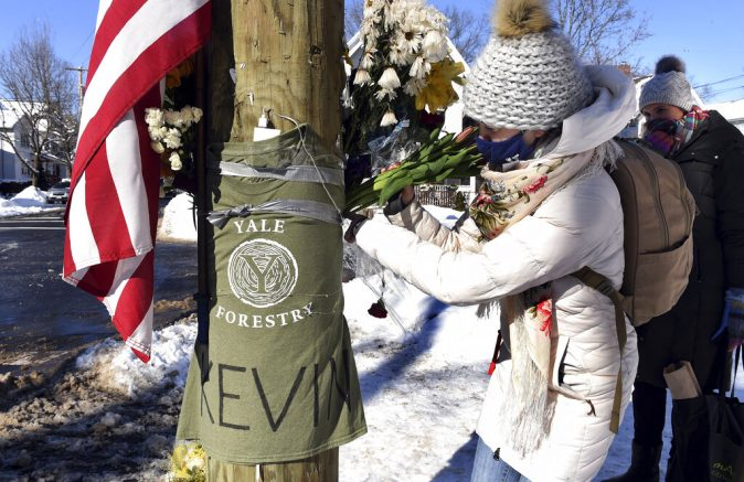 Yale postdoctoral students Maria Kochugaeva, left, and Elvira Mulyukova leave flowers at a memorial for Yale School of the Environment grad student Kevin Jiang at the corner of Lawrence and Nicoll Street in New Haven, Conn., Monday, Feb. 8, 202 near where Jiang was killed on Feb. 6, 2021. (Arnold Gold/Hearst Connecticut Media via AP)