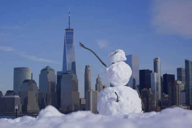A snowman sits in a field with the skyline of New York City in the background, from a park in Jersey City, N.J., Wednesday, Feb. 10, 2021. A major snowstorm pushed through the Northeastern United States on Sunday, less than a week after a storm dumped more than 2 feet on parts of the region. (AP Photo/Seth Wenig)