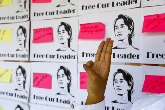 A demonstrator flashes three-fingered salute of defiance in front of a public notice board with pictures of deposed national leader Aung San Suu Kyi in Mandalay, Myanmar on Thursday, Feb. 11, 2021. Large crowds demonstrating against the military takeover in Myanmar again defied a ban on protests Thursday, even after security forces ratcheted up the use of force against them and raided the headquarters of the political party of ousted leader Aung San Suu Kyi a day earlier. (AP Photo)