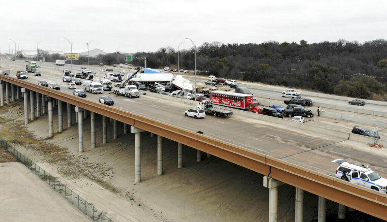First responders work the scene of a fatal crash on I-35 near downtown Fort Worth on Thursday, Feb. 11, 2021. Police say at some people were killed and dozens injured in a massive crash involving 75 to 100 vehicles on an icy Texas interstate. (Amanda McCoy /Star-Telegram via AP)