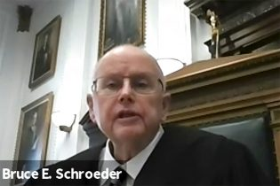 In this screen grab from live stream video, Judge Bruce Schroeder speaks in Kenosha County Court in Kenosha, Wis., on Thursday, Feb. 11, 2021, during an arrest warrant hearing for Kyle Rittenhouse. Schroeder is refusing prosecutors' request to issue a new arrest warrant for Rittenhouse who's accused of killing two people and wounding a third during a Wisconsin police brutality protest last summer. (Kenosha County Court via AP)