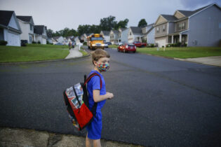 FILE - In this Aug. 3, 2020, file photo, Paul Adamus, 7, waits at the bus stop for the first day of school in Dallas, Ga. Amid mounting tensions about school reopening, the Centers for Disease Control and Prevention planned to release long-awaited guidance Friday, Feb. 12, 2021, on what measures are needed to get children back into the classroom during the pandemic. (AP Photo/Brynn Anderson, File)