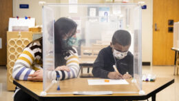 FILE - In this Jan. 11, 2021, file photo, pre-kindergarten teacher Sarah McCarthy works with a student at Dawes Elementary in Chicago. The nation's top public health agency on Friday, Feb. 12, provided a roadmap for reopening schools in the middle of a pandemic, emphasizing mask wearing and social distancing and saying vaccination of teachers is important but not a prerequisite for reopening. (Ashlee Rezin Garcia/Chicago Sun-Times via AP, Pool, File)