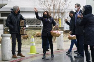 Vice President Kamala Harris arrives to deliver baskets of cookies to health care workers at the VA Medical Center in Washington, Saturday, Feb. 13, 2021. Walking with Harris at left is Secretary of Veterans Affairs Denis McDonough. (AP Photo/Patrick Semansky)